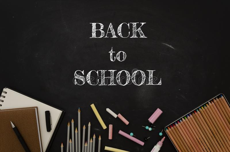 Flat lay back to school sign with tationery, notepads and pencils over classroom blackboard.  royalty free stock images