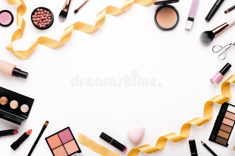 Flat lay background with female cosmetics and golden party ribbon. Copy space royalty free stock photography