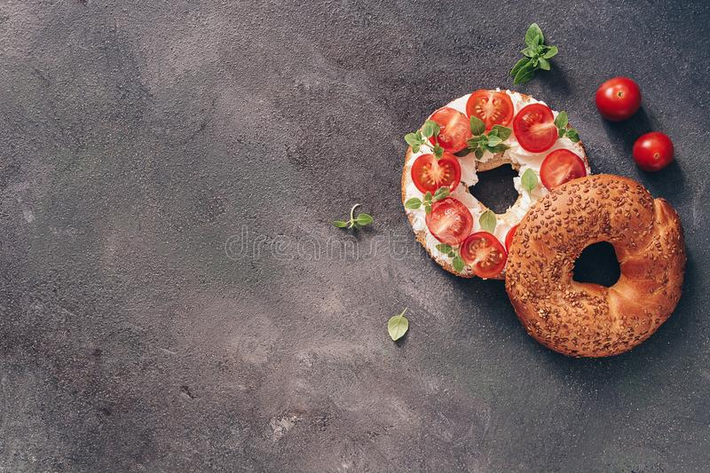 Flat lay bagel sandwich with cream cheese, cherry tomatoes and basil sprinkled with sesame and flax seeds, dark rustic background stock photo