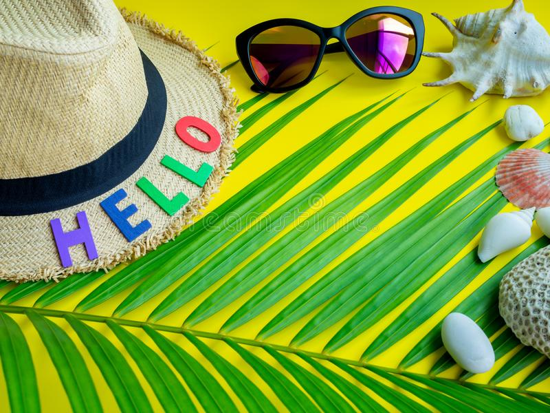 Hello Summer. Flat Lay Beach Accessories, Beach Hat, Colorful Seed Bead Necklace, Sunglasses with Hello Colourful Text, Beach Seashells, Coral, Beach Pebbles and royalty free stock images