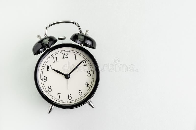 Flat lay of black alarm clock on texture white background with copy space using as time, deadline or schedule presentation royalty free stock photography