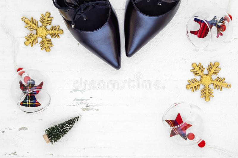 Flat lay black high heel shoes, mini christmas tree and Christmas ornaments on grunge white wood background, Merry Christmas and. Winter season fashion royalty free stock image