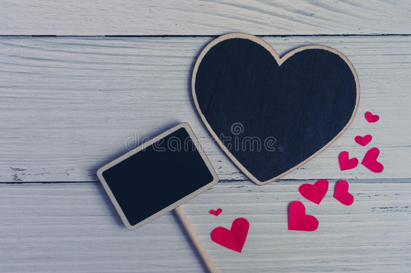 Flat lay of black plain heart sign with red hearts on white wooden vintage background. Simple and minimal flat layout style. Copy space for photography and royalty free stock image