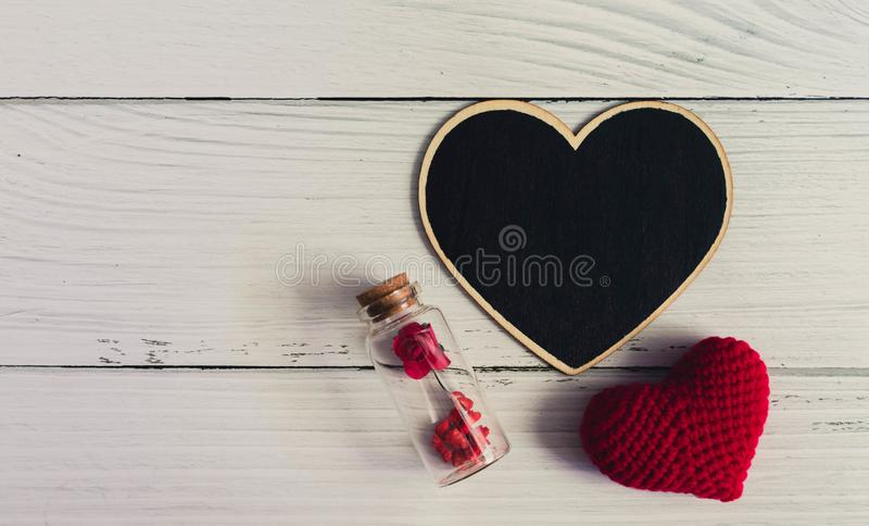 Flat lay of black plain heart sign with red heart and rose on white wooden vintage background. Simple and minimal flat layout style. Copy space for photography stock images