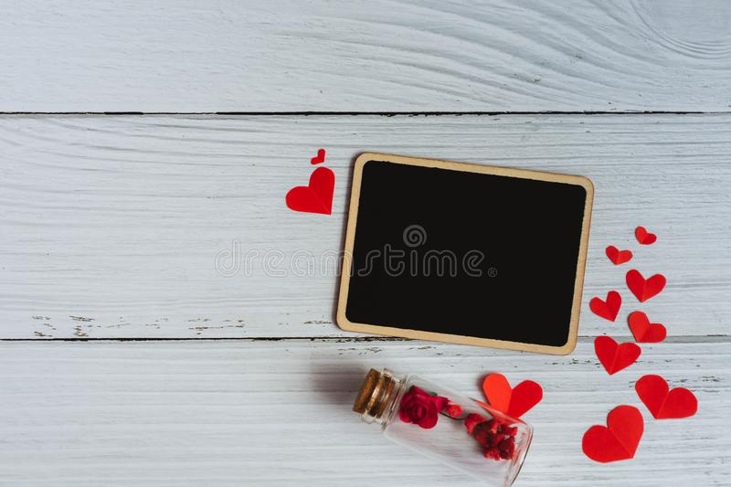 Flat lay of black plain sign with red hearts and rose on white wooden vintage background. Simple and minimal flat layout style. Co. Py space for photography and stock photo
