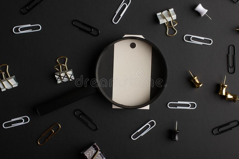 Flat lay, black style. Layout with white gift-box gift, Stationery set on black background. Design.  royalty free stock photo
