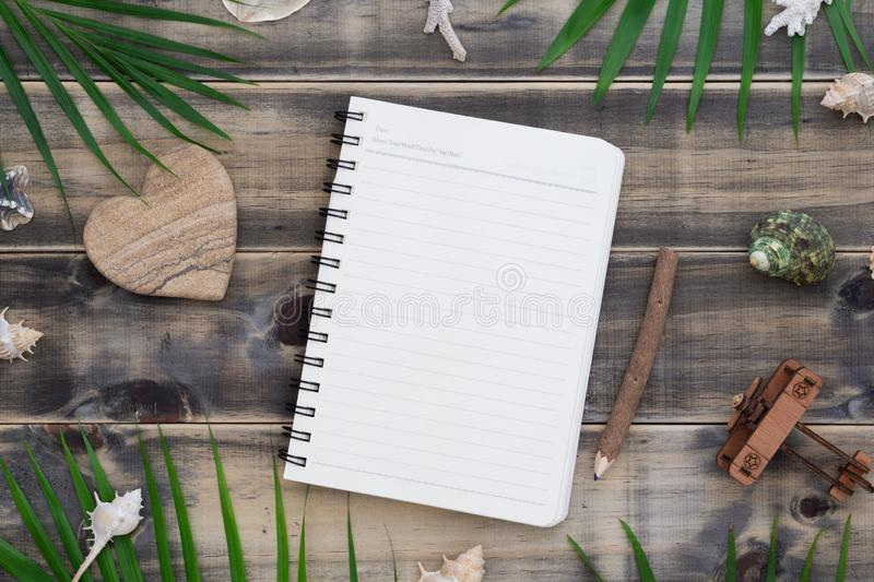 Flat lay blank notepad with heart shape rock, shells, palm leaves and air plane model. Holiday tropical beach travel vacation royalty free stock photo