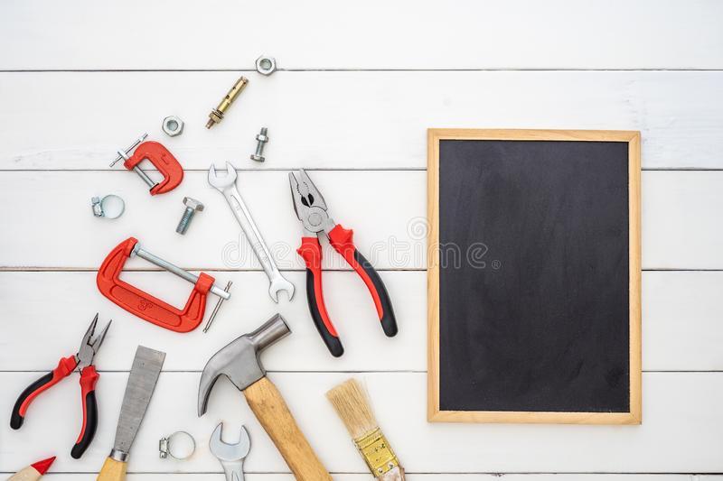 Flat lay of blank space blackboard with construction handy tools over wooden background. Top view with copy space for your stock photos