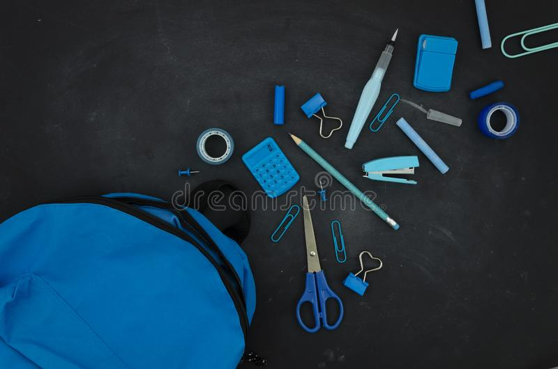 Flat lay blue stationery supplies with a school bag on a blackboard background. Top view back to school concept stock photos