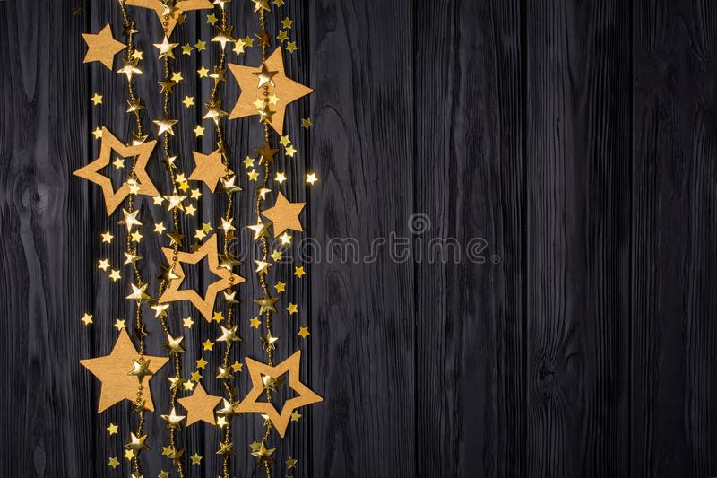 Flat lay border of big and small stars of confetti. Festive decor on a black. Flat lay border of big and small stars of confetti. Golden beads in the form of royalty free stock photography