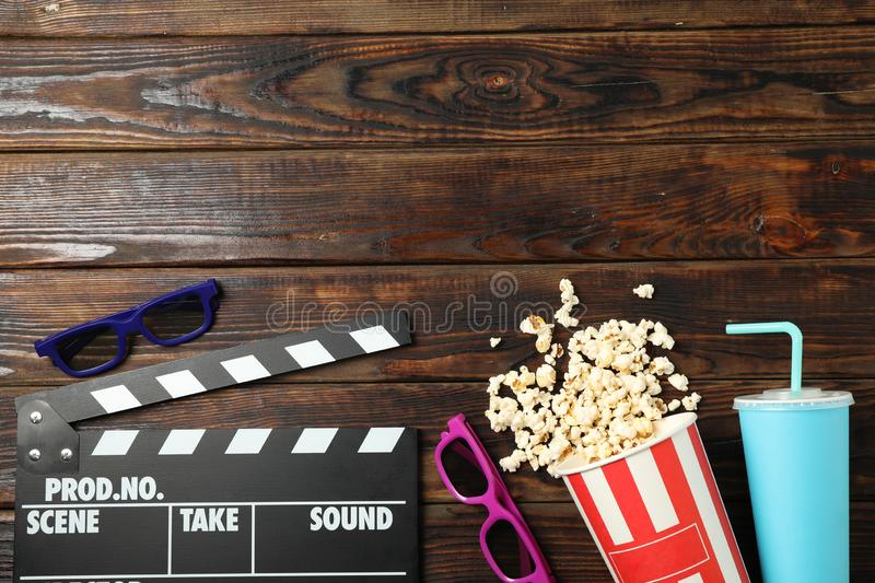 Flat lay. Bucket with popcorn, clapperboard, 3d glasses and drink on wood. Background stock photos