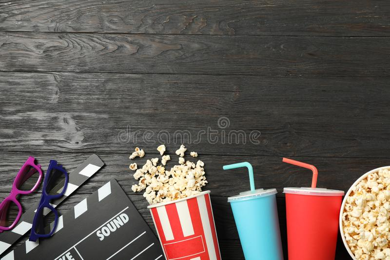 Flat lay. Buckets with popcorn, clapperboard, 3d glasses and drinks on wood. Background royalty free stock images