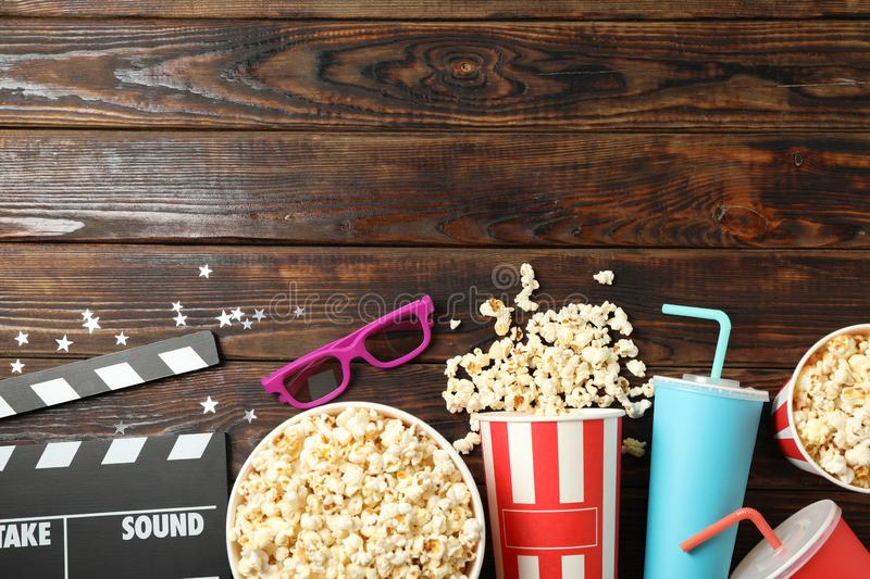 Flat lay. Buckets with popcorn, clapperboard, 3d glasses and drinks on wood. Background royalty free stock image