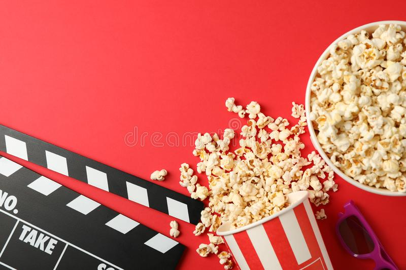 Flat lay. Buckets with popcorn, 3d glasses and clapperboard. On red background stock photo
