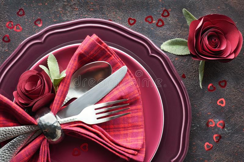 Flat lay with burgindy plates and crockery decorated with paper roses, Christmas or Valentine dinner setup. Flat lay with burgindy plates and crockery decorated royalty free stock photo
