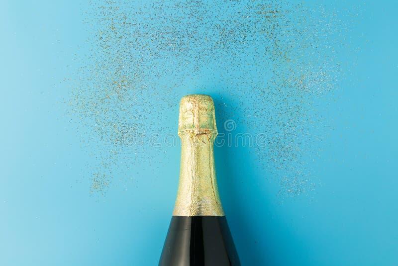 Flat lay of celebration, Champagne bottle on blue background with glitter. Flat lay of celebration, Champagne bottle on blue background with glitter royalty free stock photo