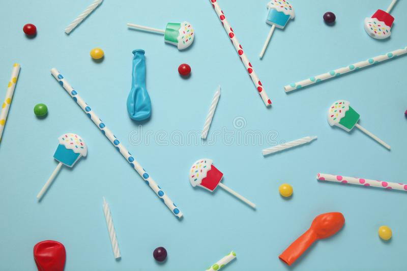 Flat lay childs birthday party, blue background pattern. Sweet candies, bright balloon, festive candles, cupcake and straws stock photos