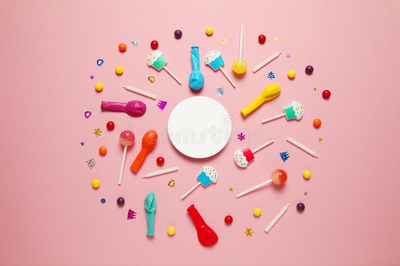 Flat lay childs birthday party, pink background pattern. Sweet candies, bright balloon, festive candles, cupcake and straws stock images
