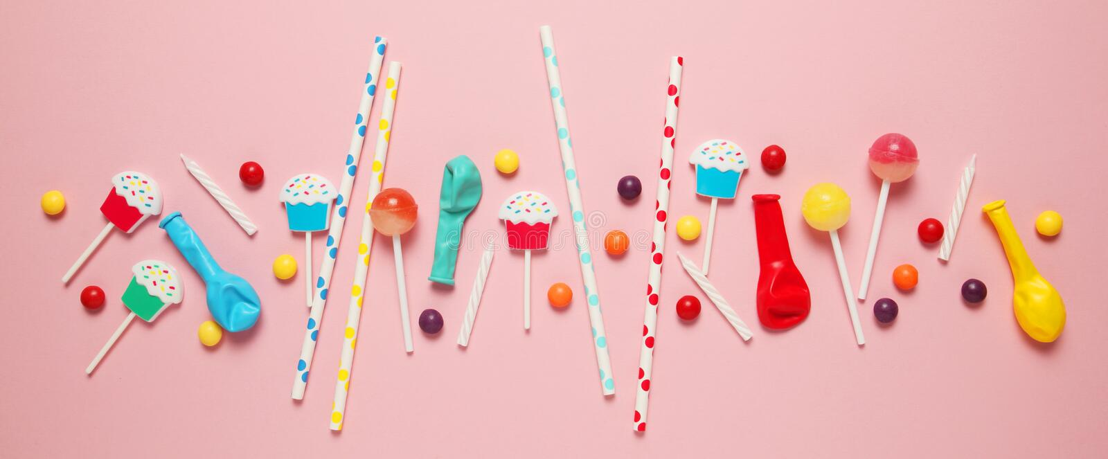 Flat lay childs birthday party, pink background pattern. Sweet candies, bright balloon, festive candles, cupcake and straws stock image