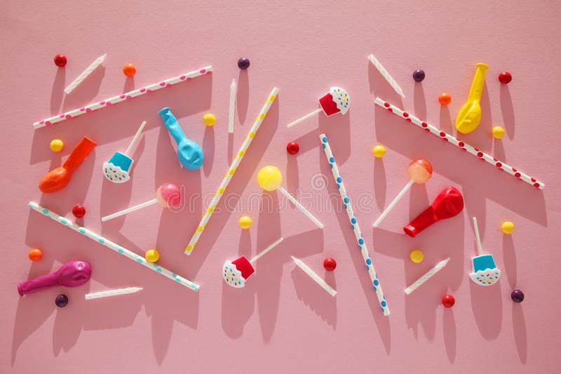 Flat lay childs birthday party, pink background pattern. Sweet candies, bright balloon, festive candles, cupcake and straws stock photos