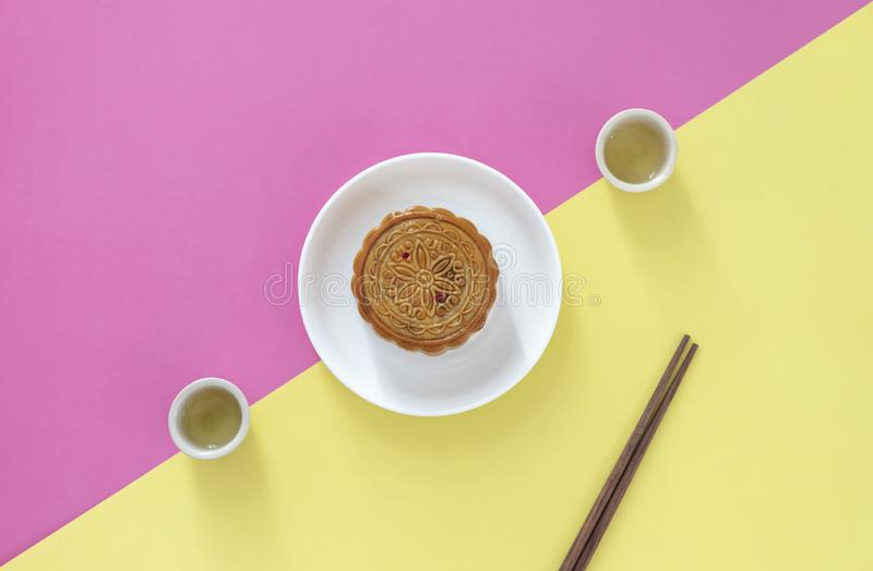 Flat lay of Chinese Festival dessert, Mid- Autumn Festival Moon cake on colorful background with teas and chopsticks. stock photos