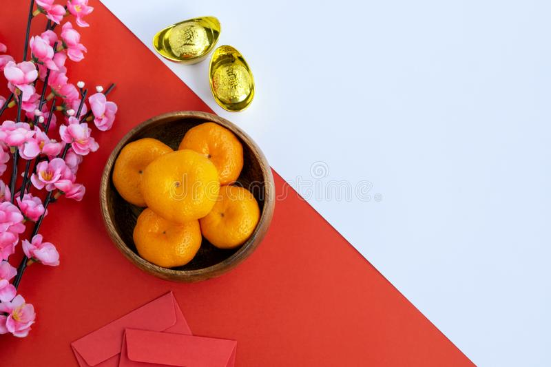 Flat lay Chinese New Year Background. Cherry Blossom, Mandarin Orange, Red Envelop and Golden Ingots on dual tone background red and white stock images