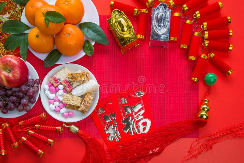 Flat lay Chinese new year festival decorations. Texts in image meaning good fortune. Flat lay Chinese new year festival decorations with orange apple grape and stock photography