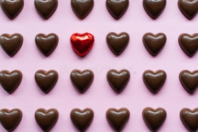 Flat lay with chocolate hearts featuring one candy in a red foil standing out. Love, valentines, present, gift, shaped, day, saint, holiday, celebration stock photo