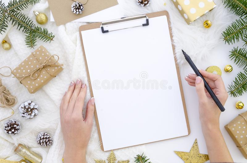 Flat lay christmas clipboard mockup. Woman`s hands holds black brush pen. Blank white paper sheet clip board mock up stock images