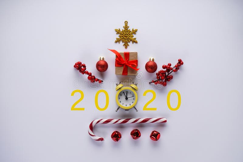 New Year celebration time 2020. Christmas decoration and yellow vintage alarm clock on a gray background. Christmas clock. Flat lay of Christmas clock, candy royalty free stock photos