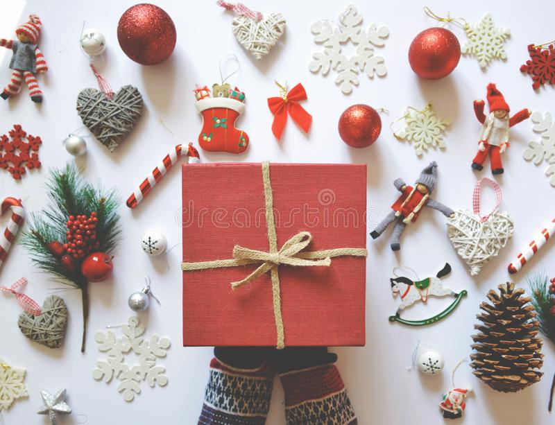 Flat lay of Christmas decoration and ornaments on white backgroundand woman hand holding red gift box - Trendy minimal flat lay stock photos