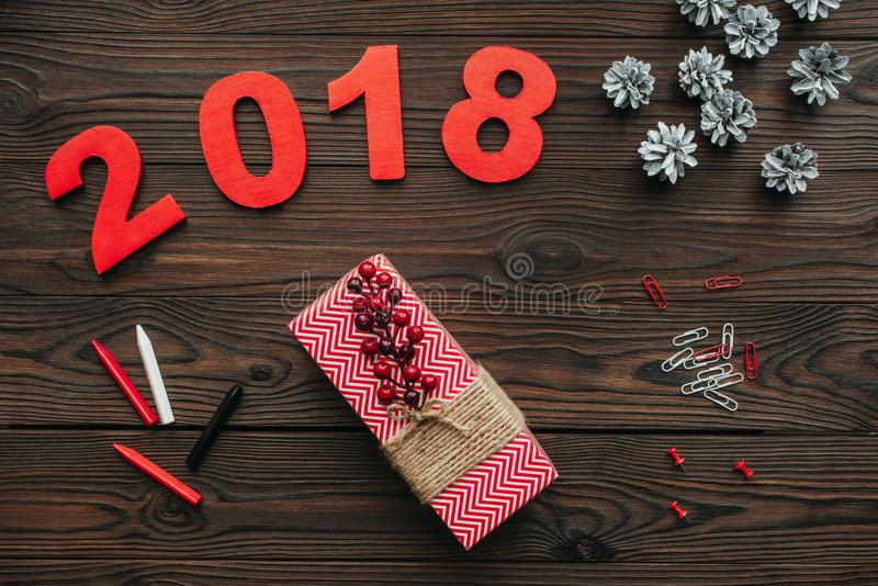Flat lay with christmas gifts, pine cones and 2018 year sign on dark. Wooden tabletop royalty free stock images