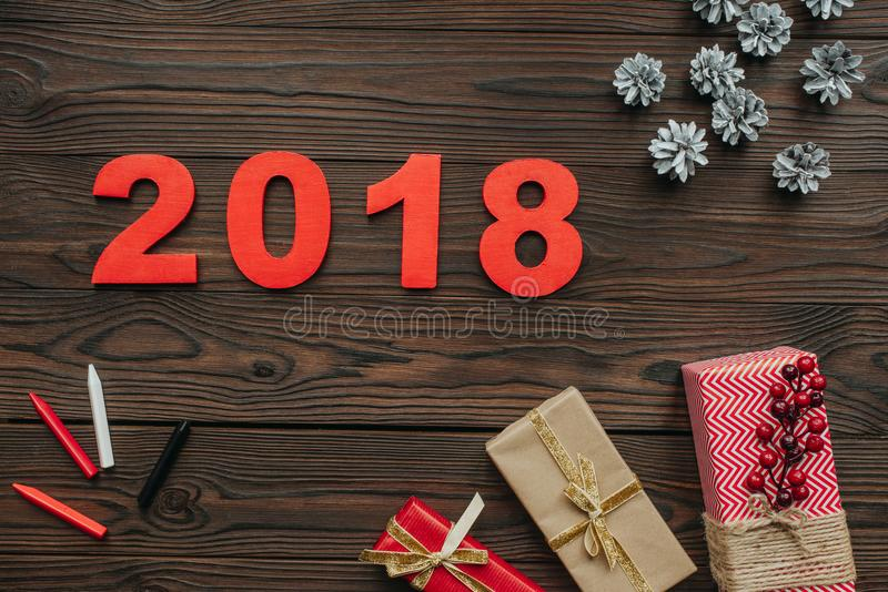 Flat lay with christmas gifts, pine cones and 2018 year sign on dark. Wooden tabletop stock image