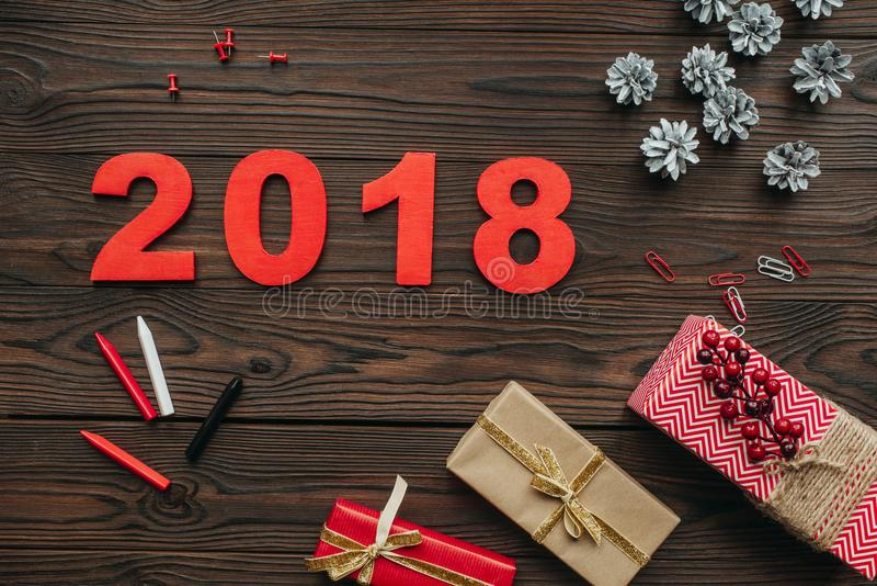 Flat lay with christmas gifts, pine cones and 2018 year sign on dark. Wooden tabletop stock photo