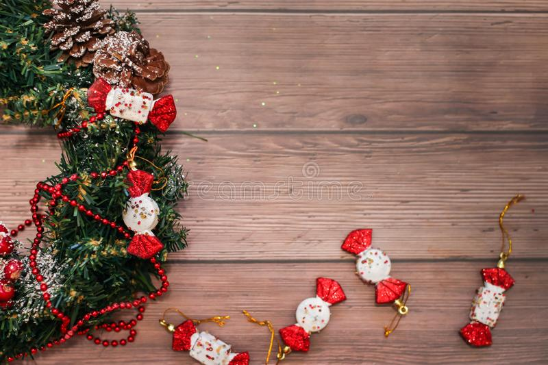 Flat lay of Christmas wreath with bumps and red decor on wooden table. Holidays christmas and new year background stock photography