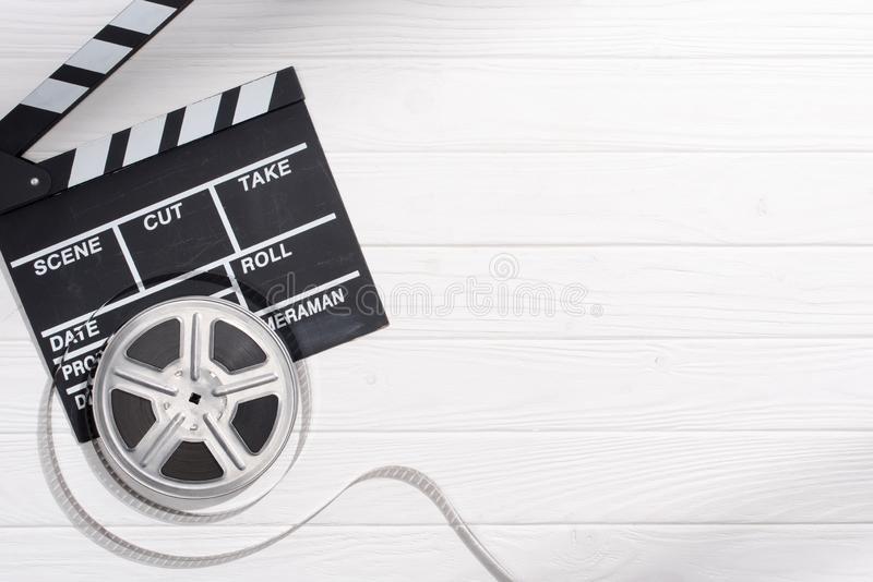 flat lay with clapper board and filmstrips on white wooden tabletop stock photos