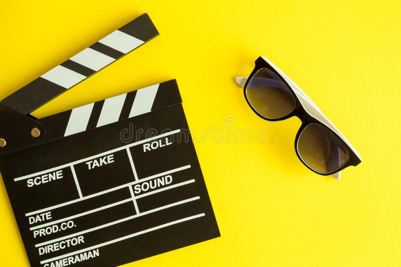 Flat lay of clapper board and glasses isolated on yellow royalty free stock photos