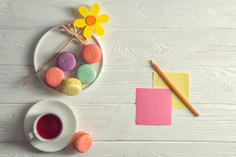Flat lay. Close up. Bright colorful french macarons, yellow felt flower, a cup of berry tea, a pencil, stickers. Copy space royalty free stock image