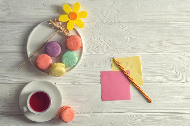 Flat lay. Close up. Bright mood. Colorful french macarons, yellow felt flower, a cup of berry tea, a pencil, stickers. Copy space royalty free stock photos