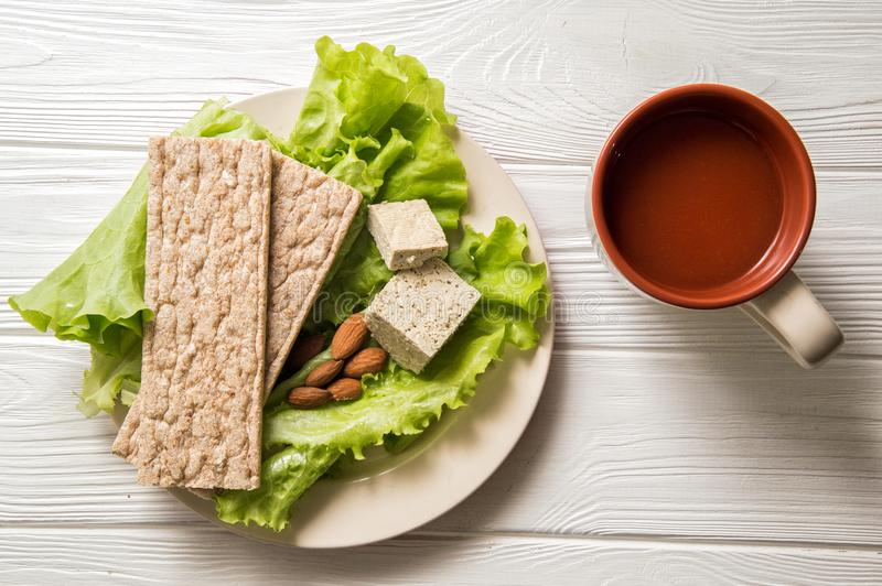 Flat lay. Close up. Dietary vegan snack consisting of green lettuce, a piece of tofu, a handful of almonds, yeast free bread. Flat lay. Close up, still life royalty free stock images
