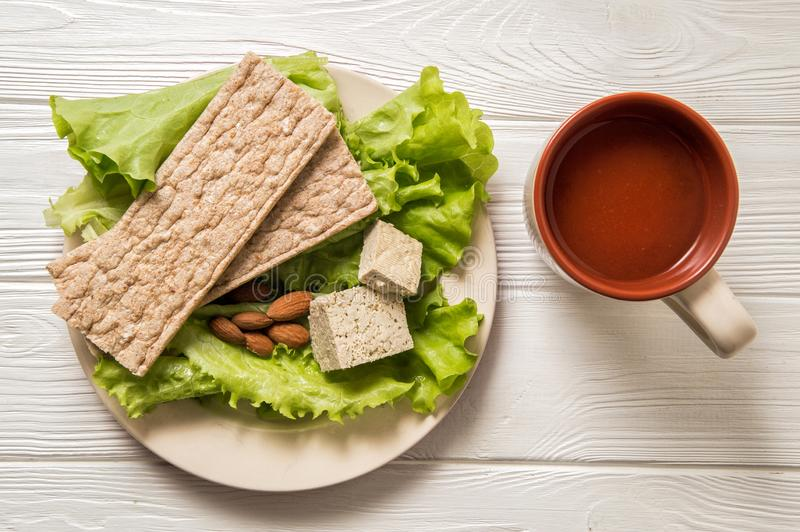 Flat lay. Close up. Dietary vegan snack consisting of green salad, a piece of tofu soy cheese, a handful of almonds royalty free stock images