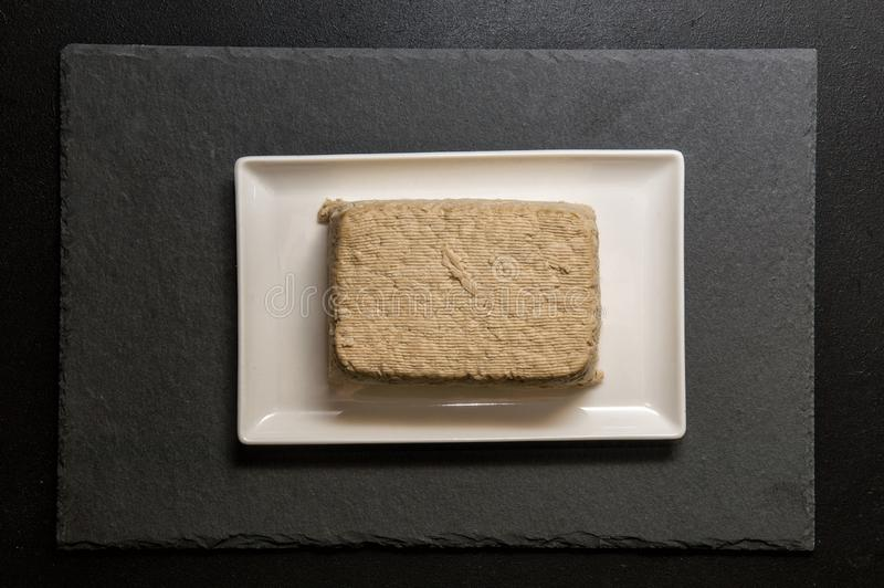 Flat lay. Close up. Japanese food. A piece of tofu, a protein-rich soy cheese, on a white rectangular plate. Black background stock photography