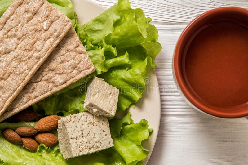 Flat lay. Close up. Dietary vegan snack consisting of green lettuce, tofu, almond, bread without yeast, tomato juice. Flat lay. Close up, still life. Dietary stock image