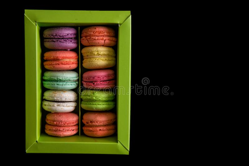 Flat lay. Close up. Sweet and colorful french macarons set in a light green box, isolated on a black background. Copy space royalty free stock photos