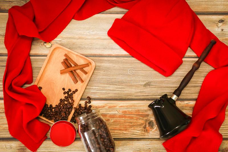Flat lay of Coffee beans, cinnamon, turk, red knitwear on wooden background. Christmas evening background royalty free stock images