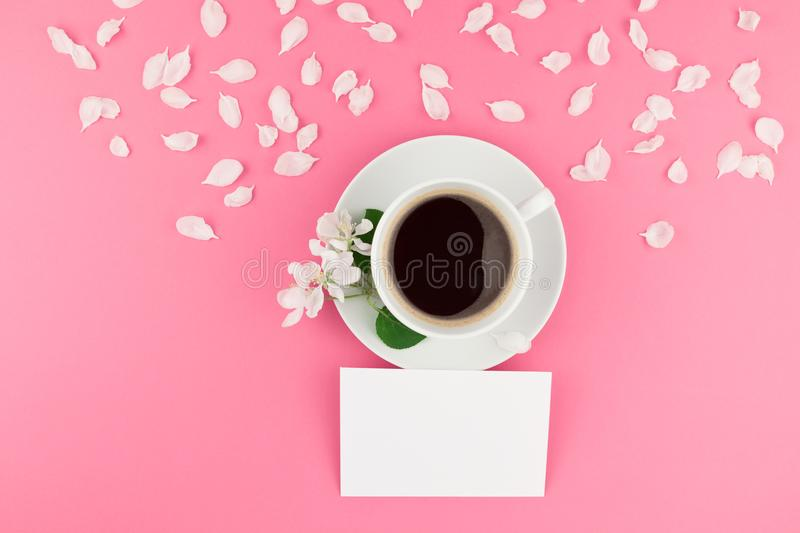 Flat lay of coffee, letter mockup and white petals stock image