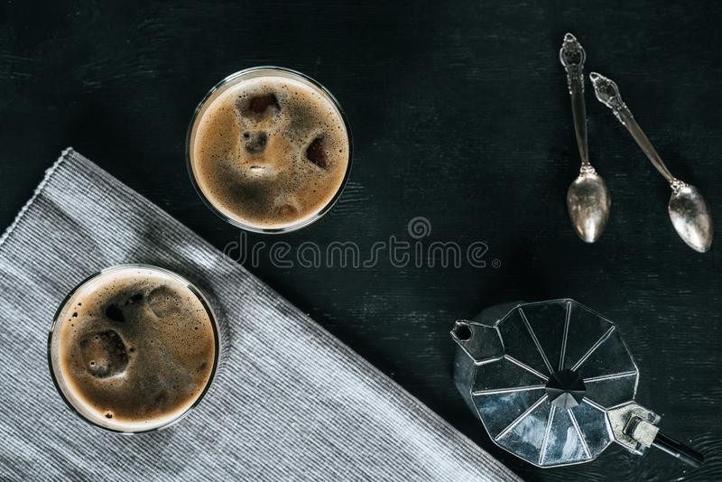 Flat lay with coffee maker, glasses of cold iced coffee and spoons. On black tabletop royalty free stock photography