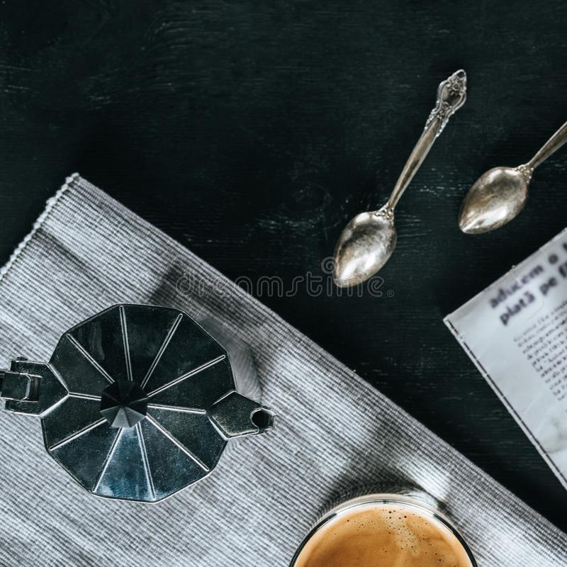 Flat lay with coffee maker, spoons and glass of cold iced coffee. On black tabletop stock images