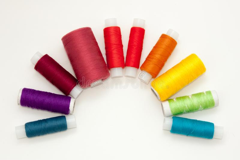 Flat lay with colorful cotton thread spools, embroidery yarn, rainbow bobbins, mock up, top view. Layout mockup on blank white royalty free stock photo