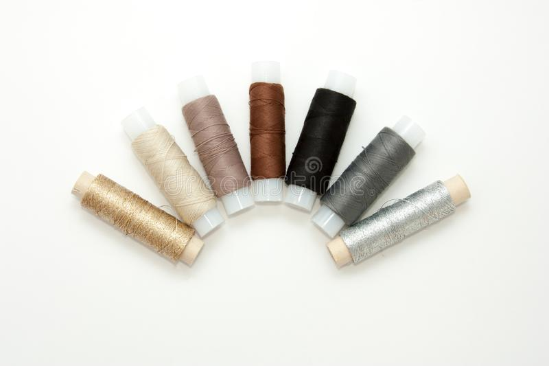 Flat lay colorful cotton thread spools, embroidery yarn, white, brown, gray, black, silver, gold bobbins, mock up, top view. stock photography